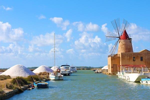 A Sicilian salt mine along a canal showing large mounds of sea salt.