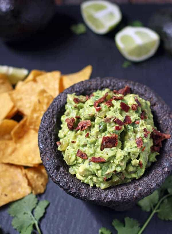 Smoked Bacon & Tomatillo Guacamole in a bowl garnished with smoked bacon