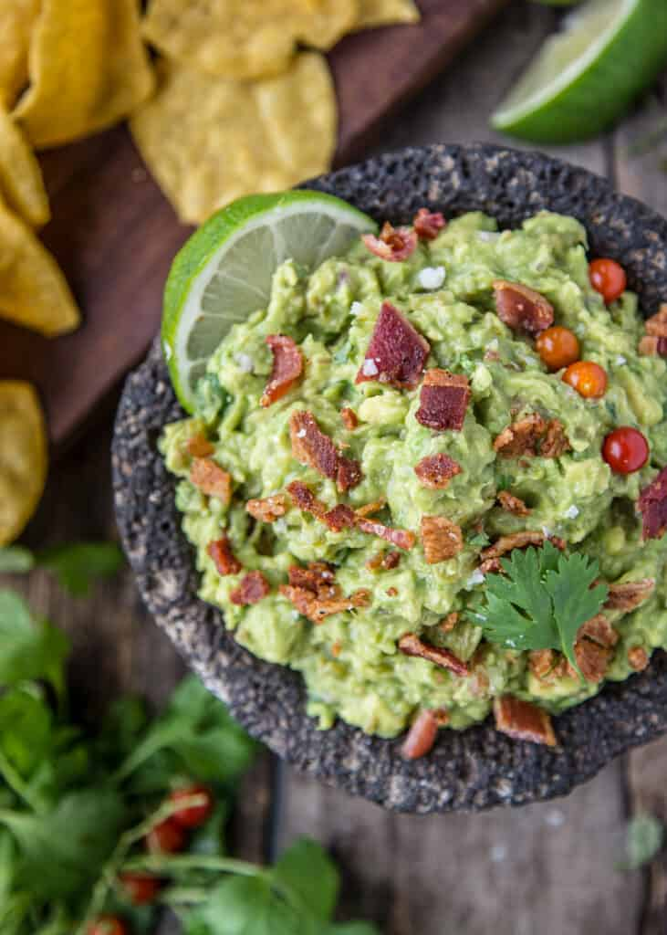A bowl full of guacamole with smoked bacon and smoked tomatillos