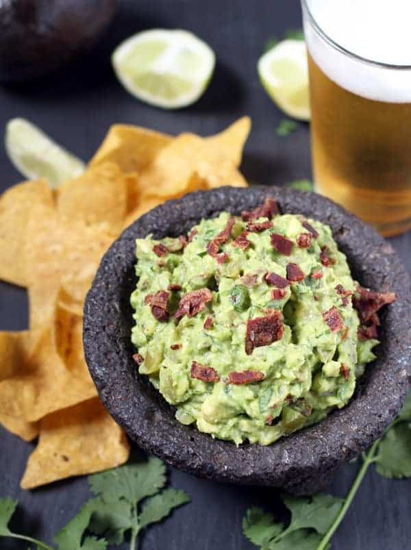 Guacamole with Smoked Bacon and Smoked Tomatillos in a black bowl with tortilla chips and a beer