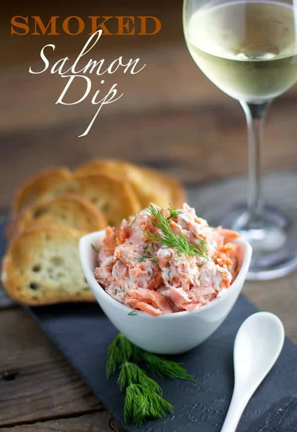 Smoked Salmon Dip in a white bowl with a glass of white wine and crostini
