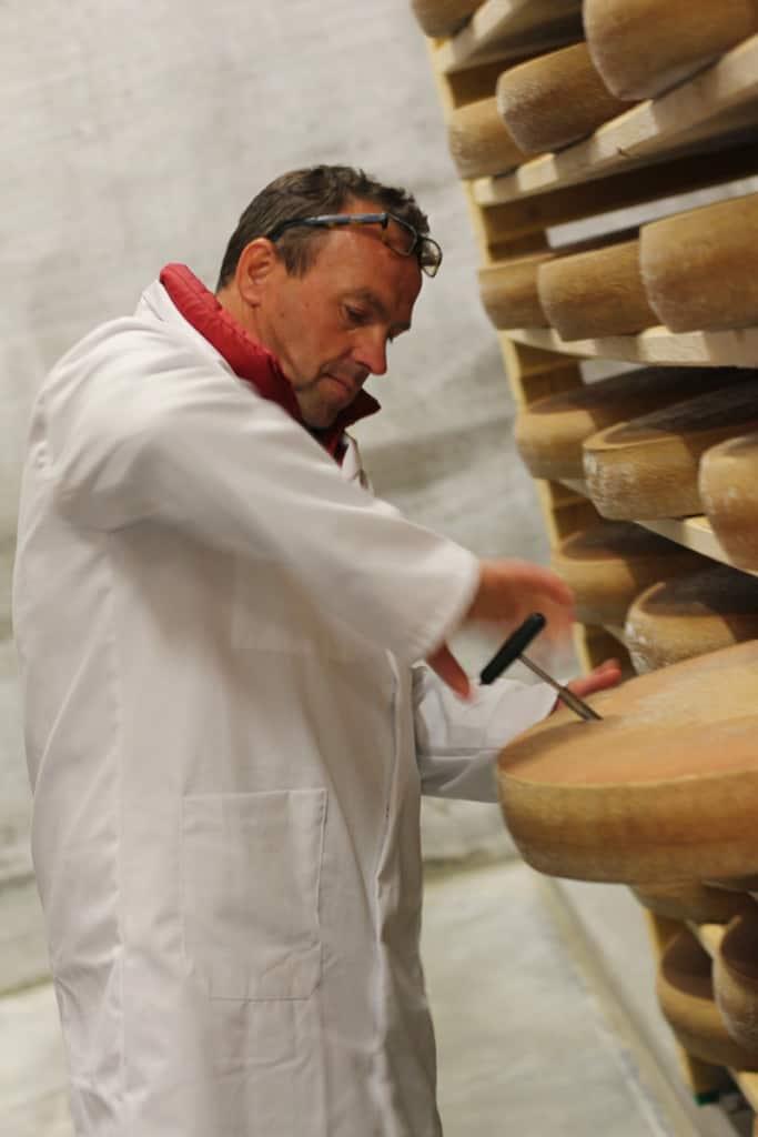 An affineur testing Comté cheese