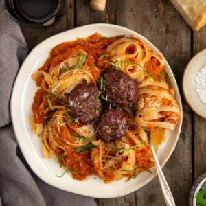 A plate with smoked tomato sauce, pasta, and meatballs