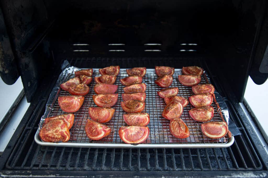 A sheet pan of tomatoes roasting on the grill