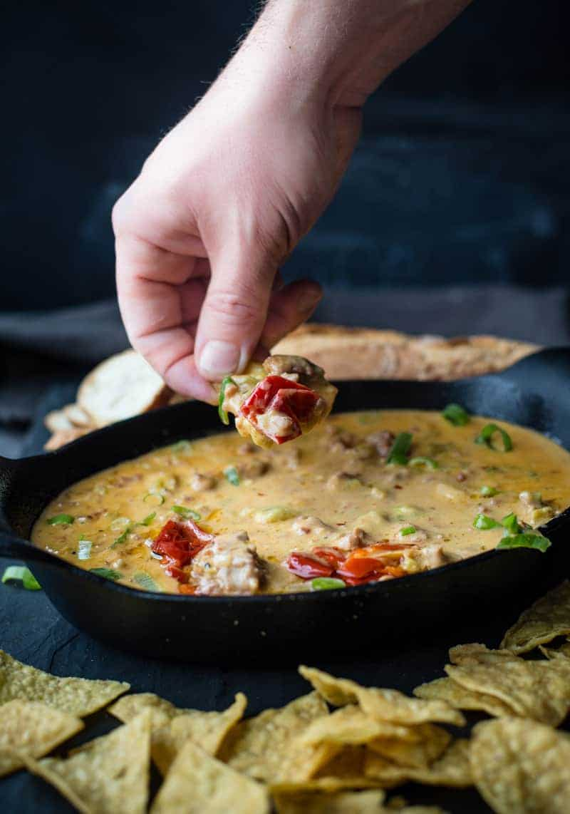Smoked Sausage and Hatch Chili Beer Cheese Dip being eaten with a tortilla chip