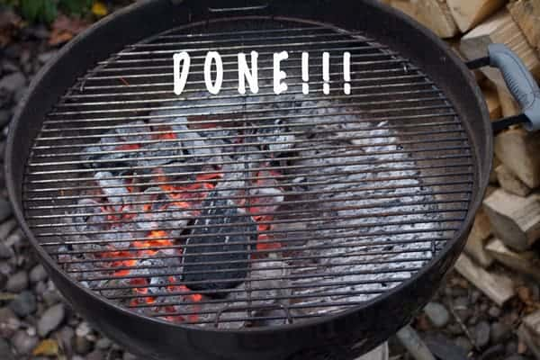 Coals burning in a kettle grill using two zone cooking.