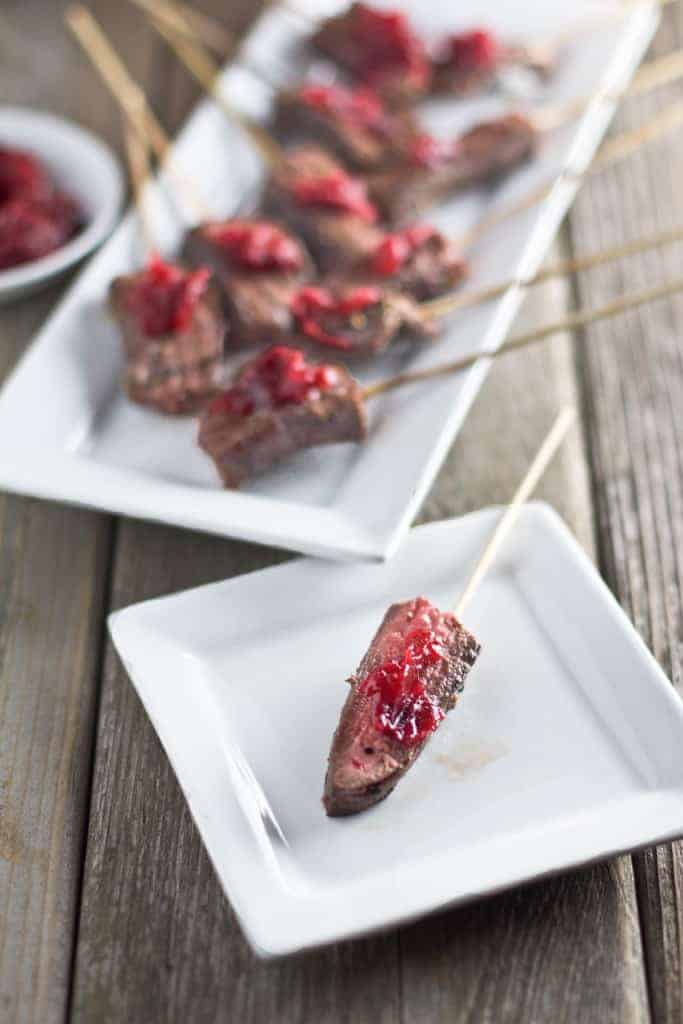 Marinated Steak Skewers. A simple appetizer filled with savory flavors, a touch of holiday sweetness, a small bit of spice, a good dose of protein, and they won't weigh you down.