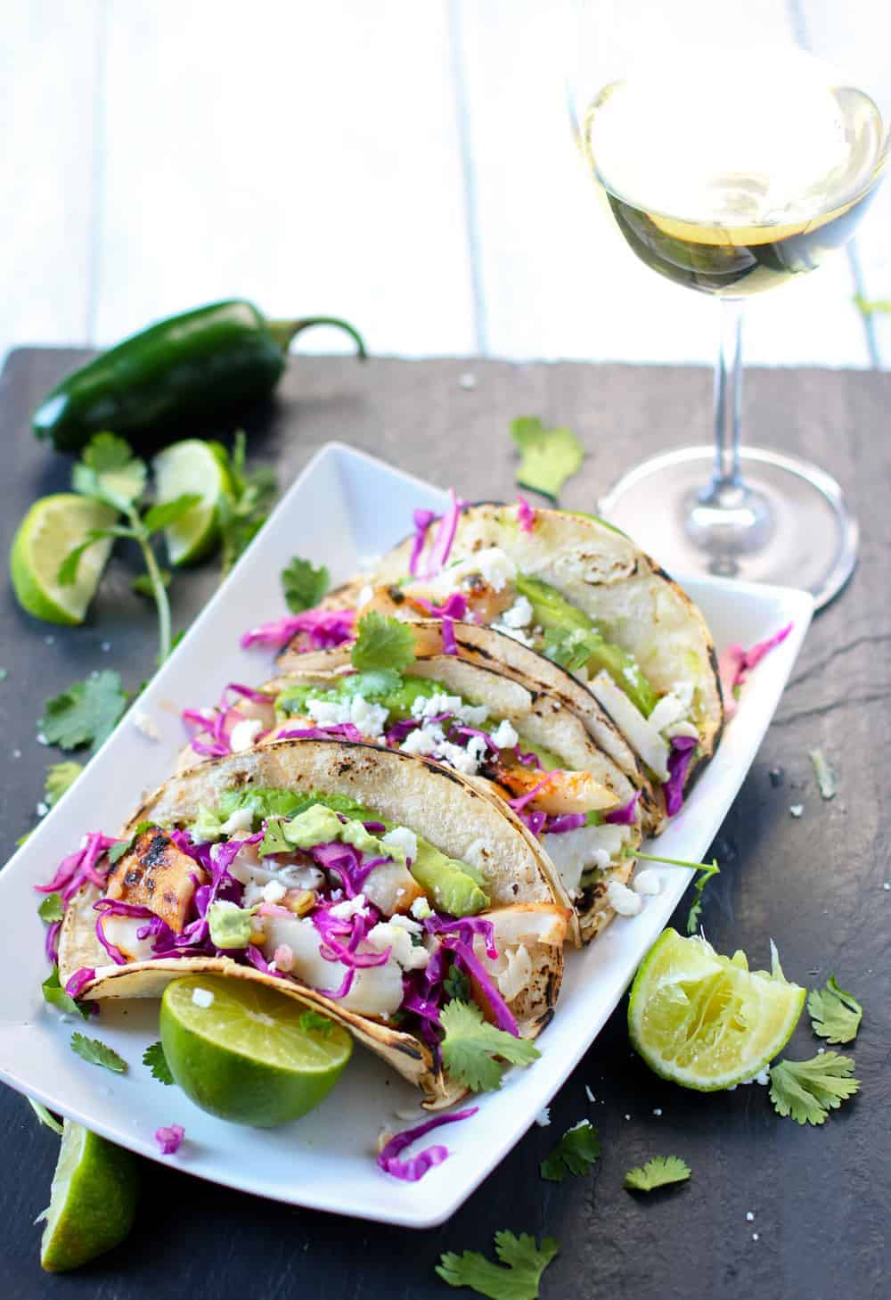 Grilled Fish Tacos on a white plate garnished with limes and cilantro, and Wine Pairing