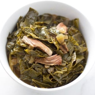collard greens with smoked turkey leg in a white bowl
