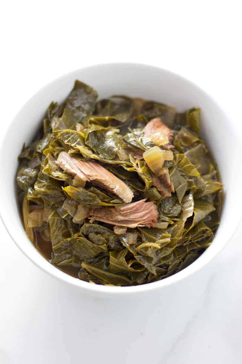 A bowl of collard greens with smoked turkey legs