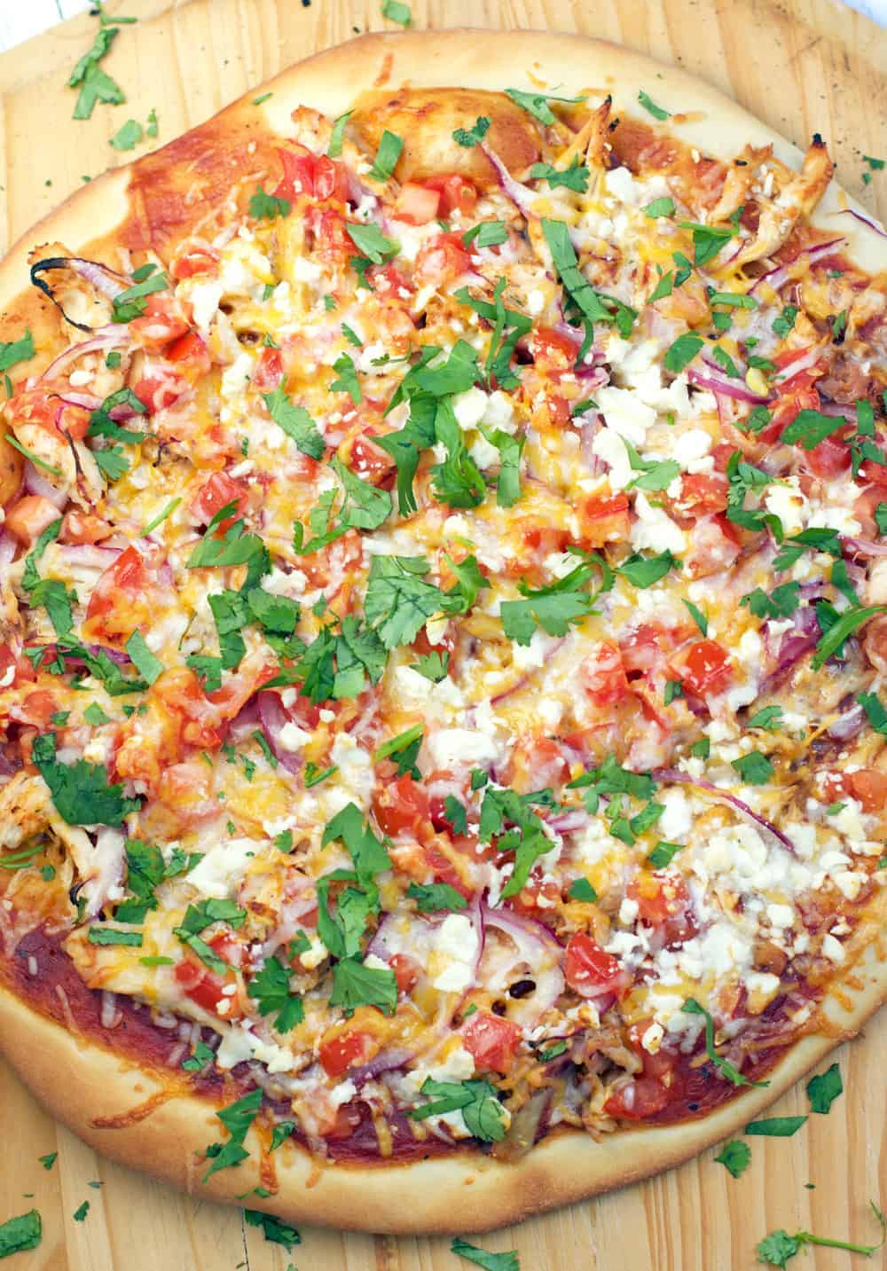 Smoked BBQ Chicken Pizza, made with real smoked chicken, a combination of delicious cheeses, onions, tomatoes, bbq sauce, and topped with fresh cilantro. Perfect for Pizza Night!!!