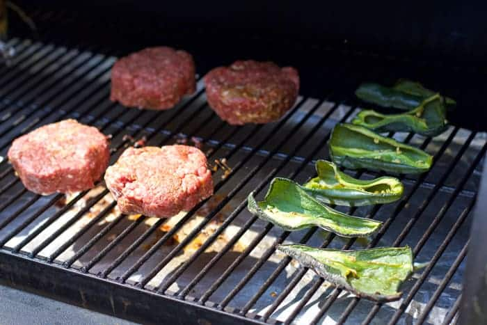 Cooking-burgers-and-poblano-peppers-on-a-smoker