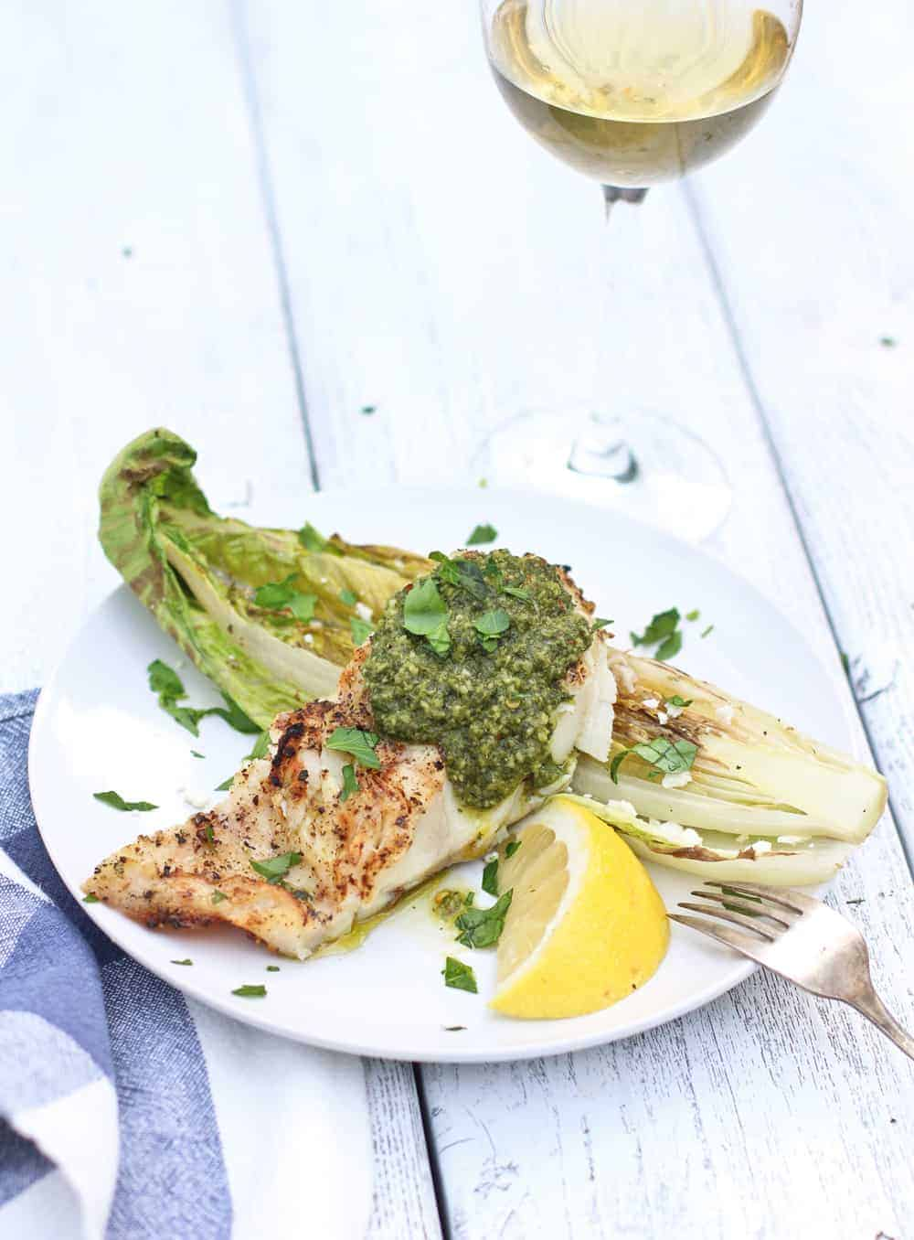 Grilled Cod Fillet with Chimichurri Sauce served on a plate with Grilled Romaine.