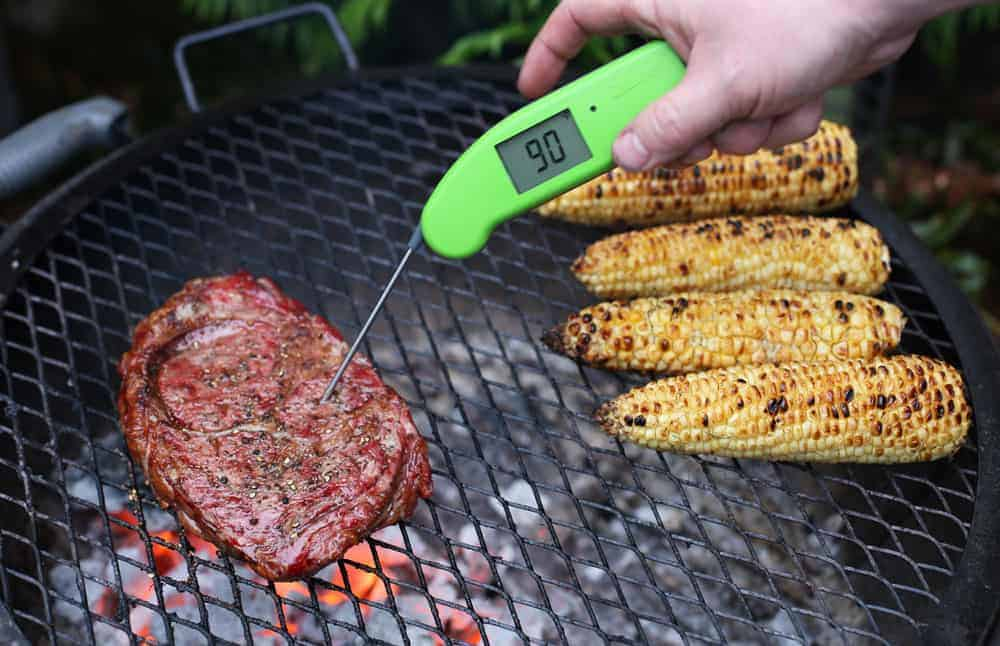Taking the temperature of a ribeye steak on a grill