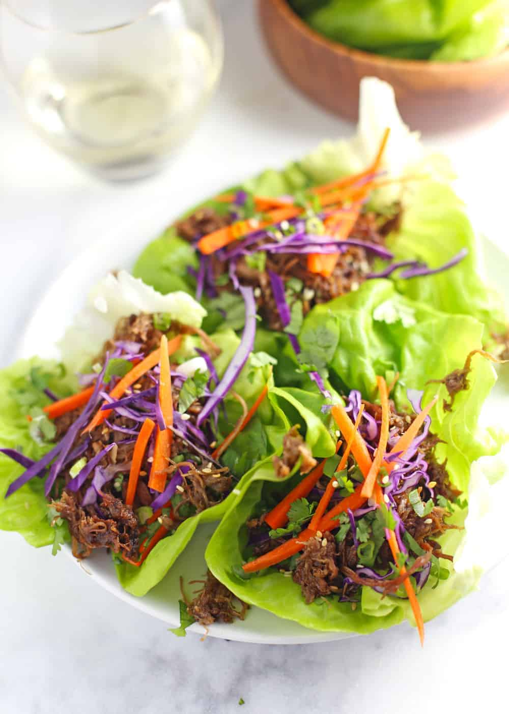 Pulled Pork lettuce wraps on a white plate, garnished with carrots and cabbage