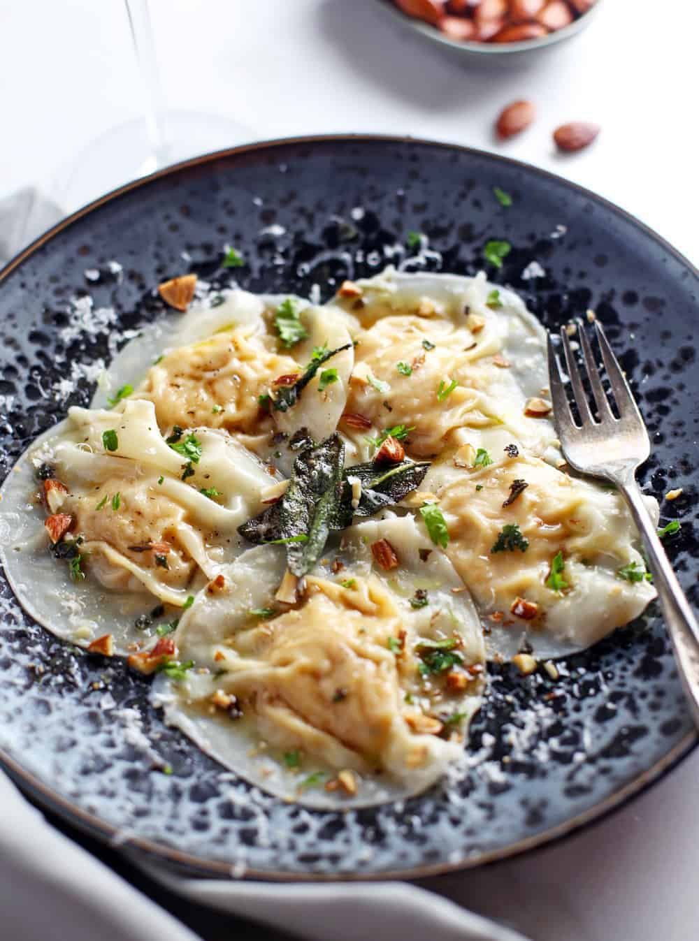 Smoked Pumpkin Ravioli, made with smoked-roasted pumpkin puree, wrapped in wonton wrappers, and topped with an indulgent and savory sage butter sauce with smoked almonds. Pure deliciousness!