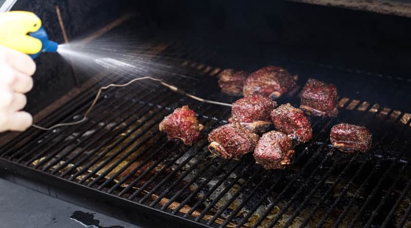 The importance of using a spritz to keep beef moist when smoking on a smoker.