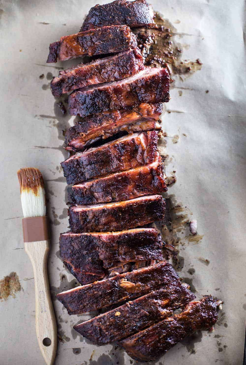 Smoked Ribs with Spicy Mango BBQ Sauce (low sugar) on parchment paper with a bbq brush to the side