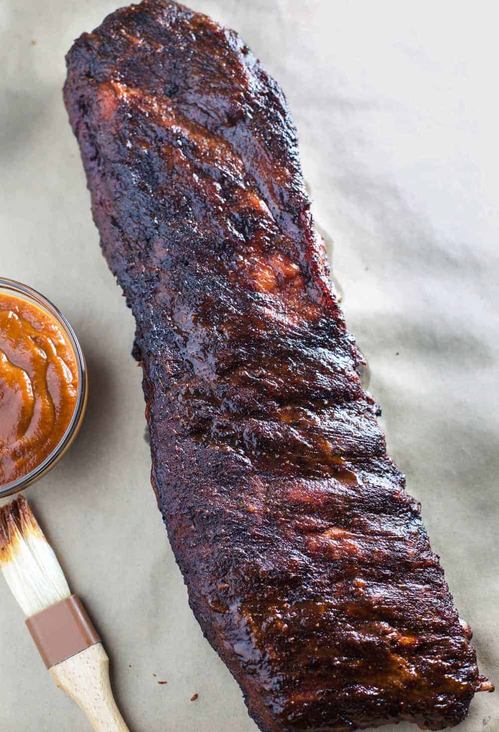 Smoked Ribs with (low sugar) Spicy Mango BBQ Sauce on parchment paper with a bbq brush to the side