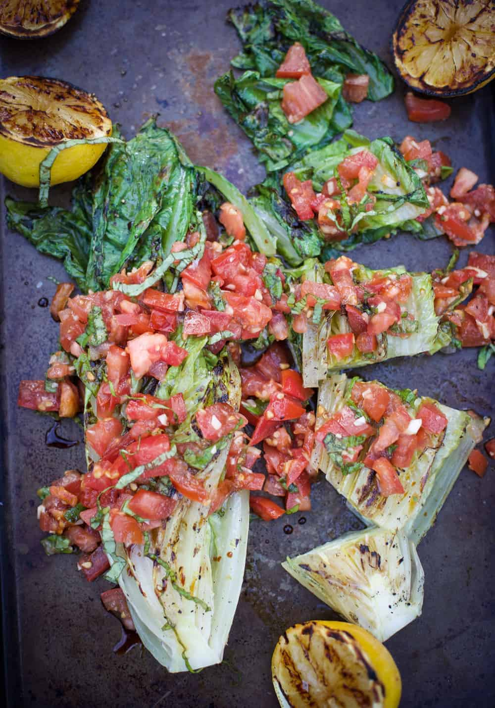 Grilled Romaine with Tomatoes, Basil, and Balsamic, garnished with grilled lemons