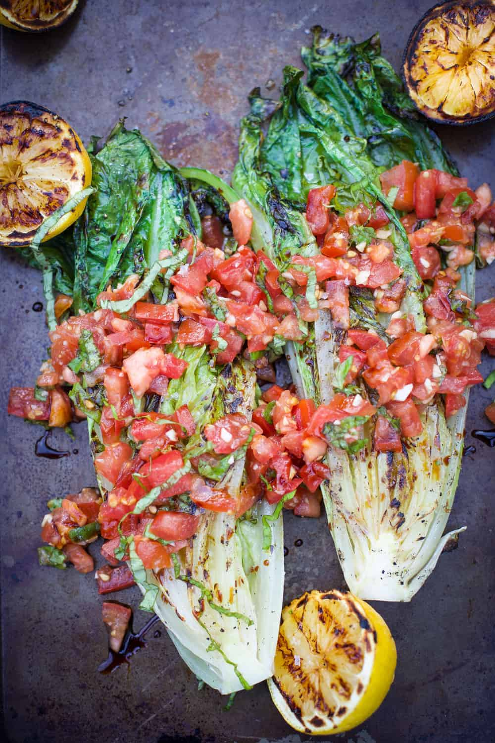 Grilled Romaine topped with Tomatoes and Basil on a sheet pan