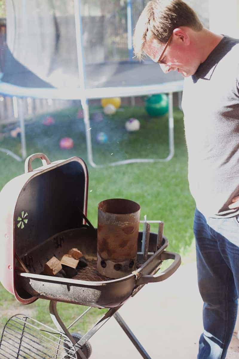 A man smoking and grilling on a tiny, old grill