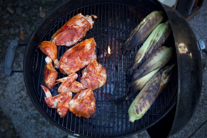 Chicken and corn cooking on a grill