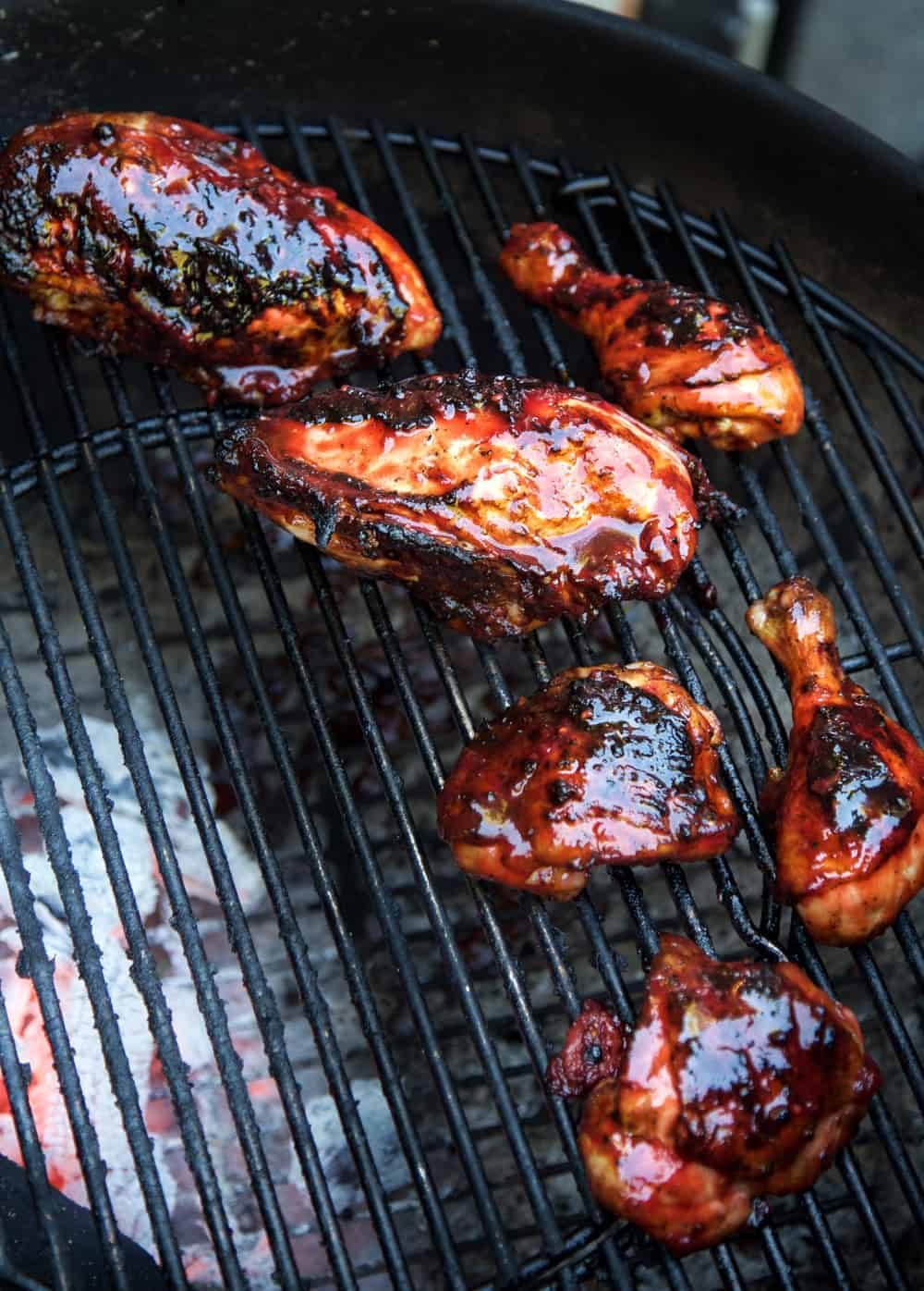 Chicken on a grill with a Blackberry BBQ Sauce over the top