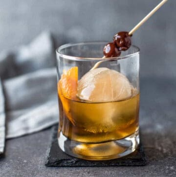 Round cube of smoked ice in a glass with an old fashioned