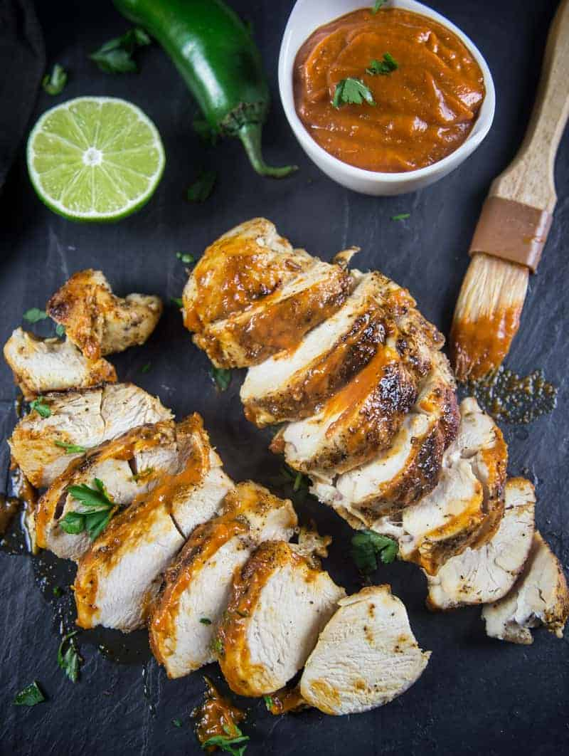 grilled chicken topped with mango bbq sauce with a jalapeno and a lime to the side