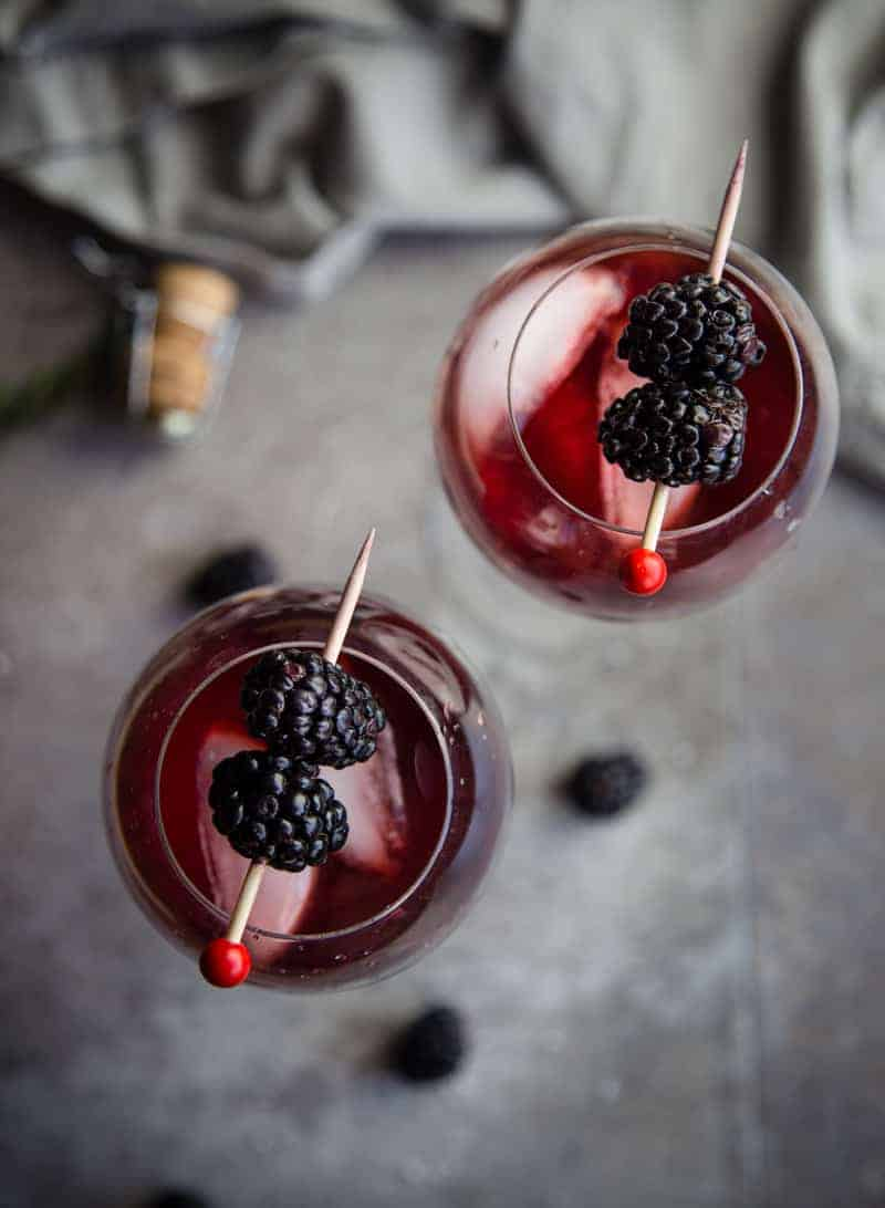 A top down photograph of two glasses filled with Blackberry Aperol Spritz Cocktail