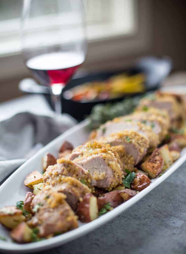 Slices of pork on a long platter with potatoes and a glass of wine