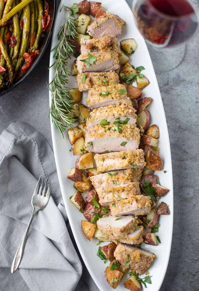 Kettle Chip Crusted Grilled Pork Tenderloin on a platter surrounded by roasted potatoes