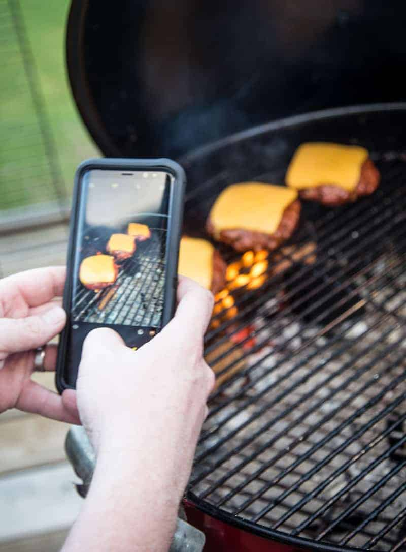 Taking a picture of grilled cheeseburgers.