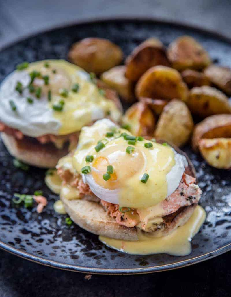 Smoked Salmon Eggs Benedict on a blue plate with roasted potatoes