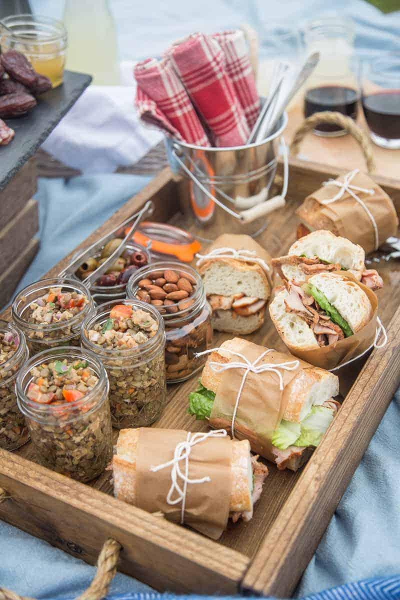 A picnic spread with cold lentil salad in mason jars and pork tenderloin sandwiches