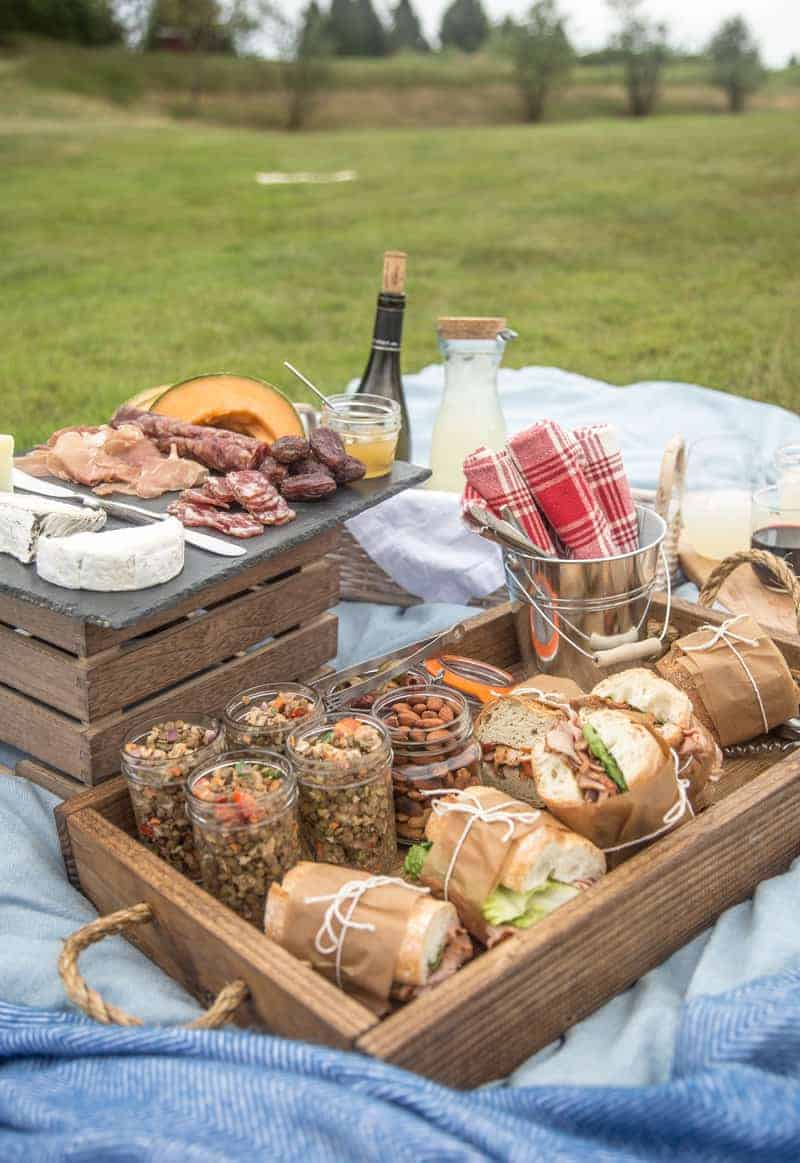A picnic spread on a blanket with pork tenderloin sandwiches and a cold lentil salad.