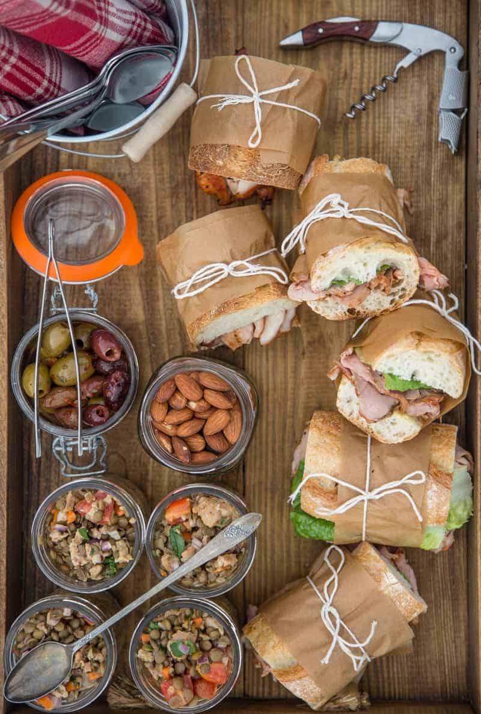 A picnic platter full of pork tenderloin sandwiches, almonds, lentil salad, and olives.