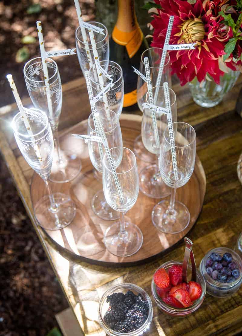 Champagne flutes with straws on a wooden tray with a bottle of prosecco, fruit garnishes in bowls, and a vase of flowers