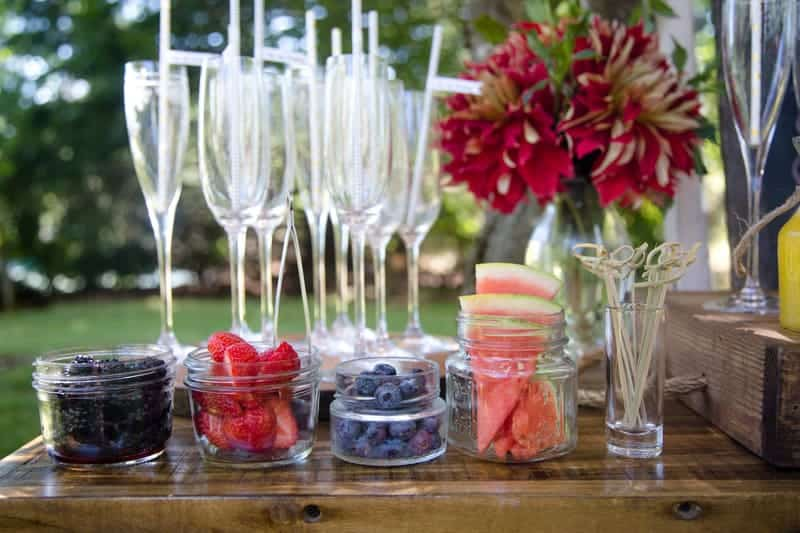 Mimosa Bar with empty glasses and jars of fresh berries