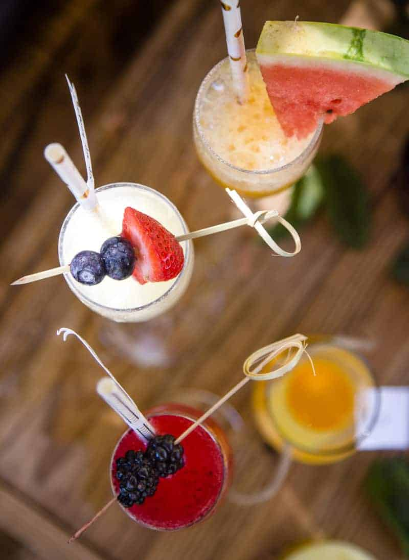Mimosas in flutes with straws and fruit garnishes