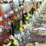 A long Thanksgiving table set with wine and wine glasses