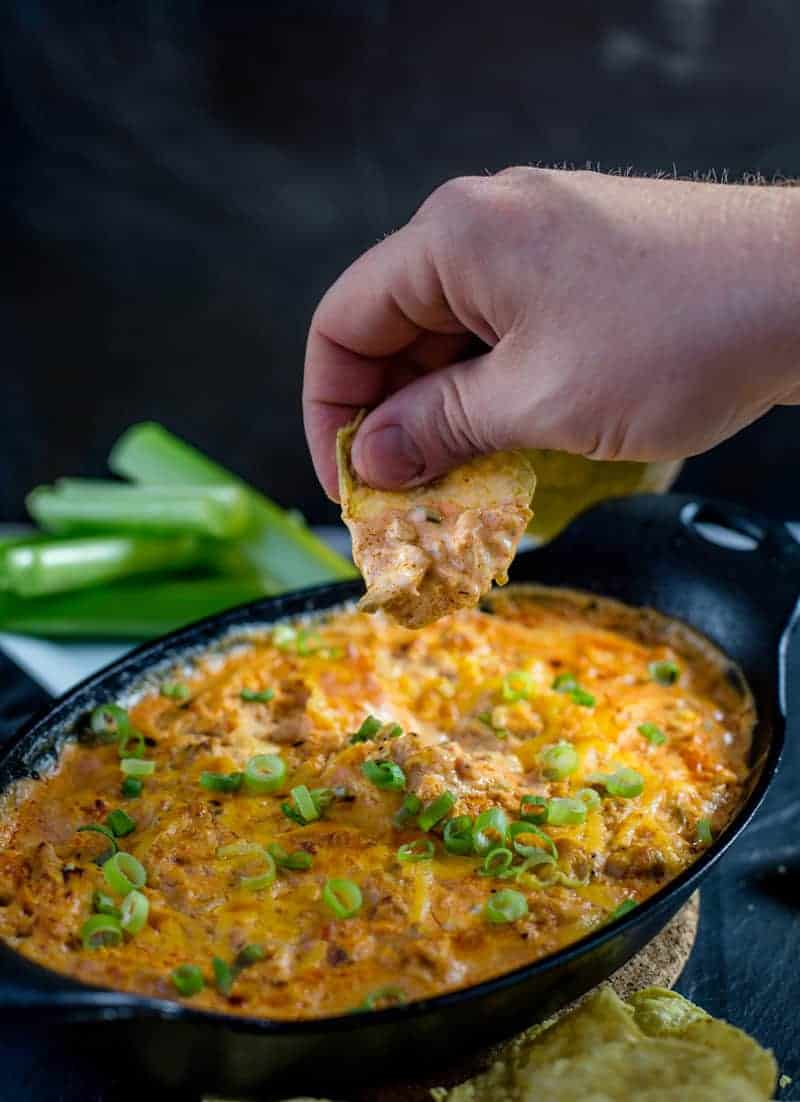 Smoked Buffalo Chicken Dip being eaten with a tortilla chip