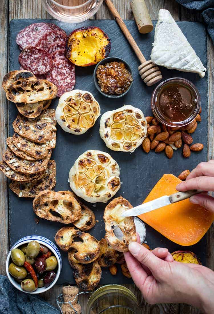 A cheese platter with baguette roasted garlic and olives
