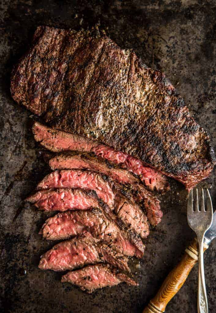 Grilled Bavette Steak sliced thin on a sheet pan.