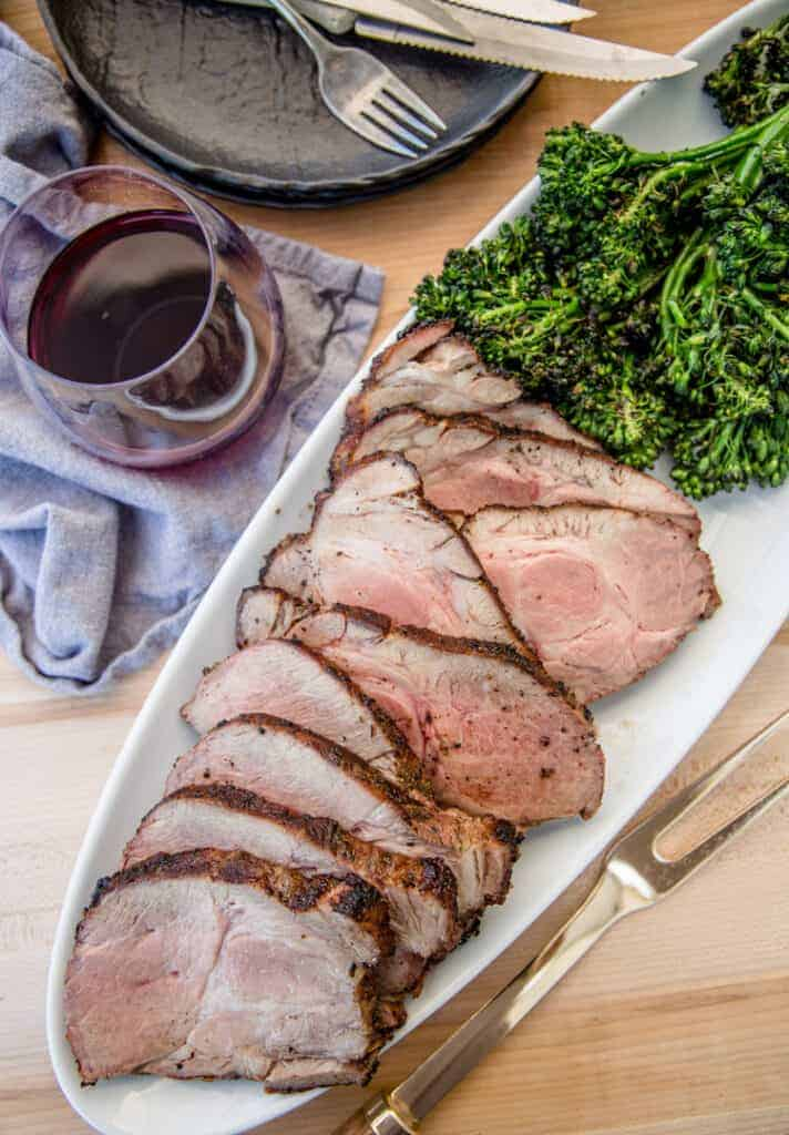Grilled pork collar cut into slices with grilled broccolini and a glass of red wine