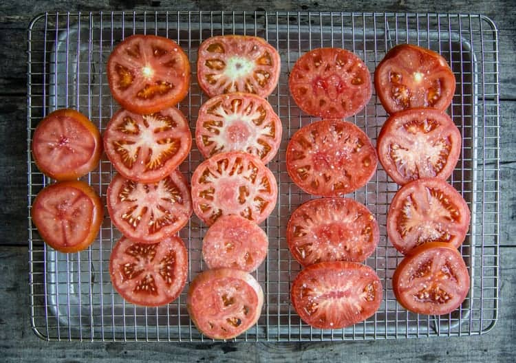 Raw sliced tomatoes salted on a cookie sheet.