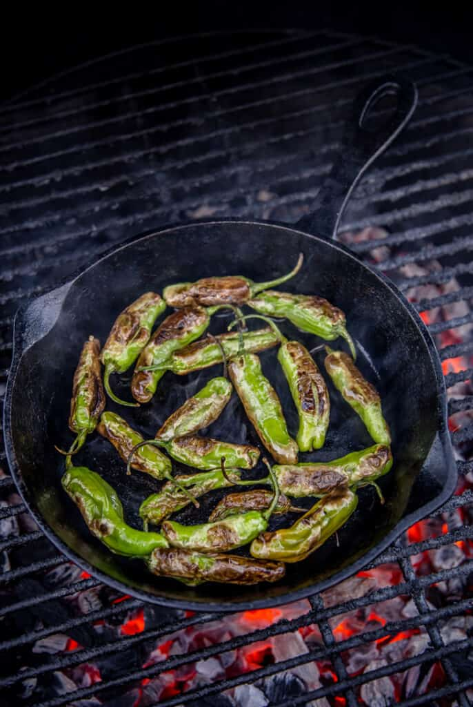 Shishito peppers being blistered in a cast iron pan on the grill