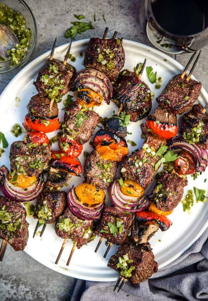 Steak Skewers with Beer Marinade and Jalapeño Parsley Chimichurri Sauce on a plate with a glass of wine.