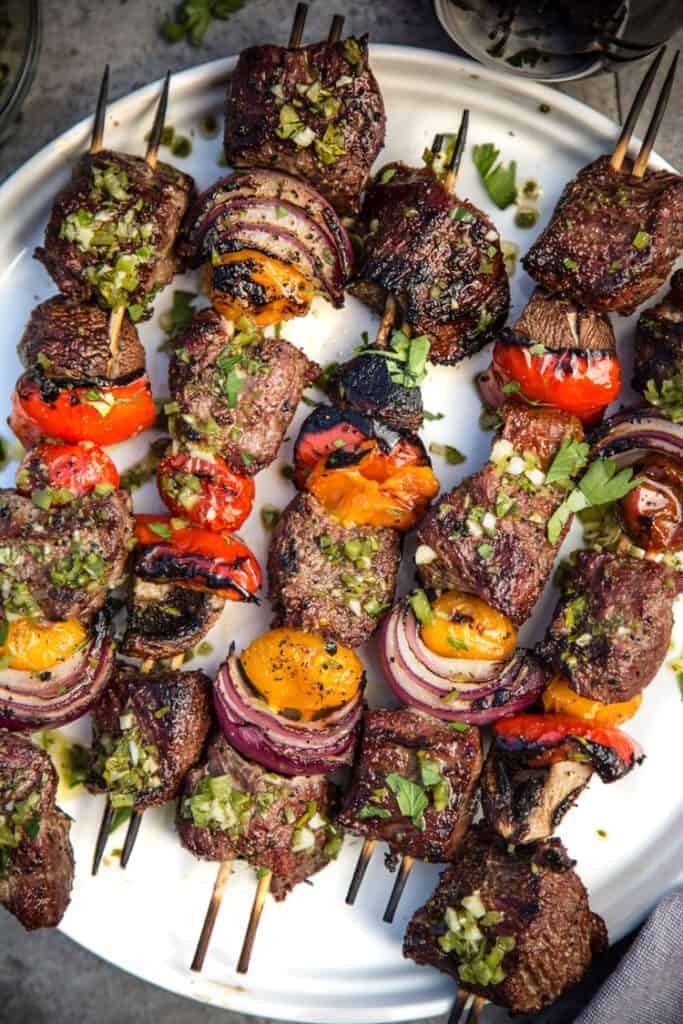 Steak Skewers with Beer Marinade and Jalapeño Parsley Chimichurri sauce on a plate.
